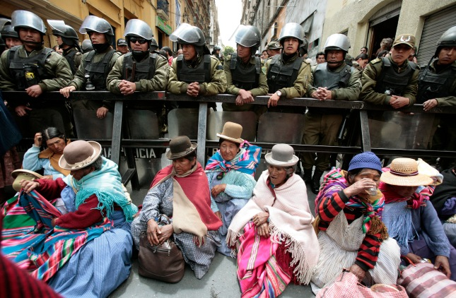 Indigenous supporters of Bolivia's President Evo Morales sit in front of police standing guard next to the Congress building in La Paz